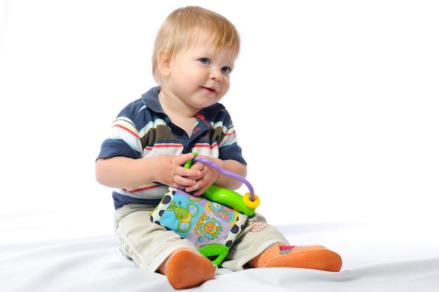 小さな幼児は愛するおもちゃで遊ぶ。ぬいぐるみを手に持った少年