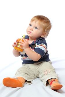 Little toddler sits and drinks water from orange bottle