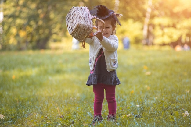 Little toddler witch playing with a basket of leaves in autumn park
