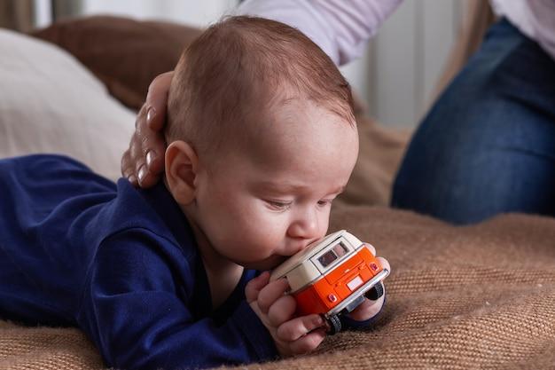 小さな幼児は、小さなオレンジ色のミニバンのおもちゃと父親の手でポートレートを閉じます。
