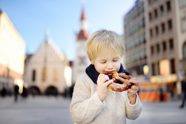 Little tourist holding traditional bavarian bread called pretzel on the town hall in munich, germany