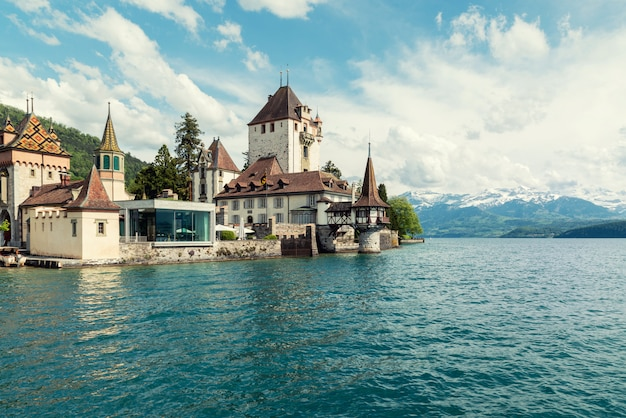Little tower of oberhofen castle in the thun lake with mountains on background in switzerland