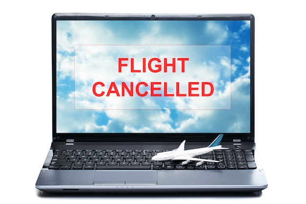 Little toy airplane on a laptop with a message - flight cancelled