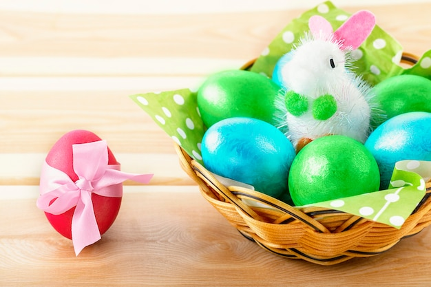 Little toy bunny in basket with decorated egg
