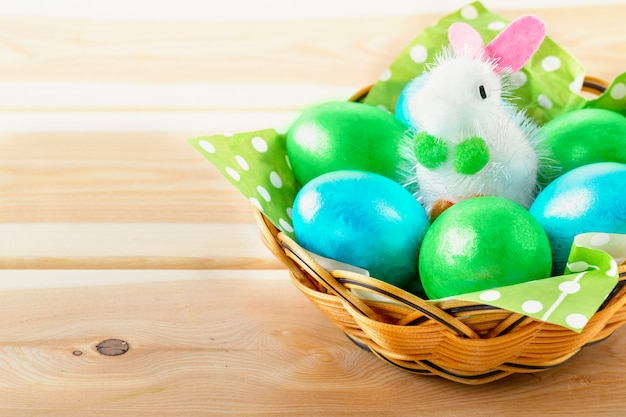 Little toy bunny in basket with decorated eggs on wooden background - easter card. copy space