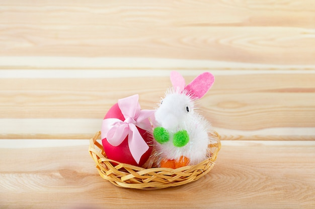 Little toy bunny in basket with  egg decorated with easter pink bow on wooden table