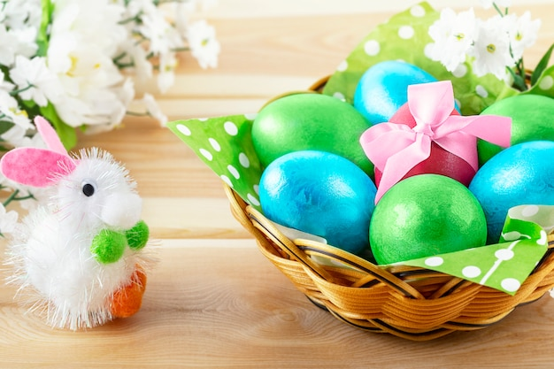 Little toy bunny on wooden table and  basket with decorated eggs
