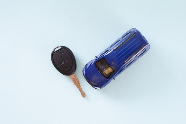 青い背景の上に横たわっている小さなおもちゃの車と鍵。カーアラーム設置コンセプト