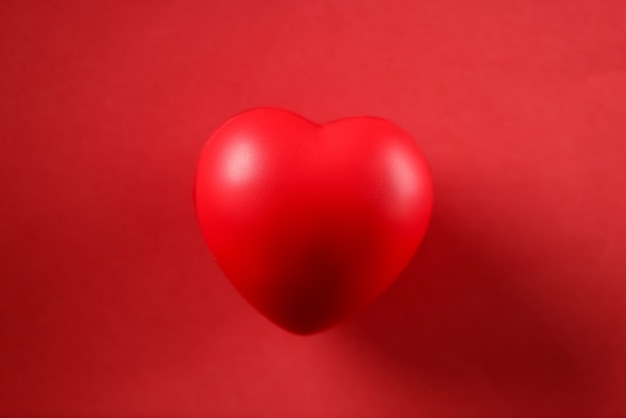 Little toy heart lying on red background closeup mockup. valentines day concept