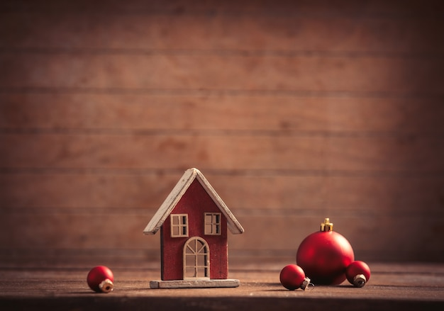 Little toy house and christmas baubles on wooden background