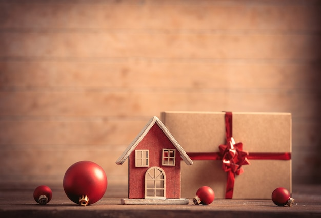 Little toy house and christmas gift on wooden table