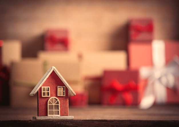 Little toy house and christmas gifts on background