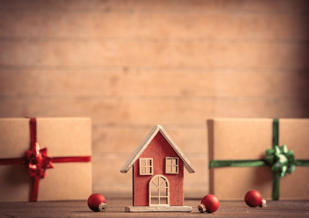Little toy house and christmas gifts on wooden table