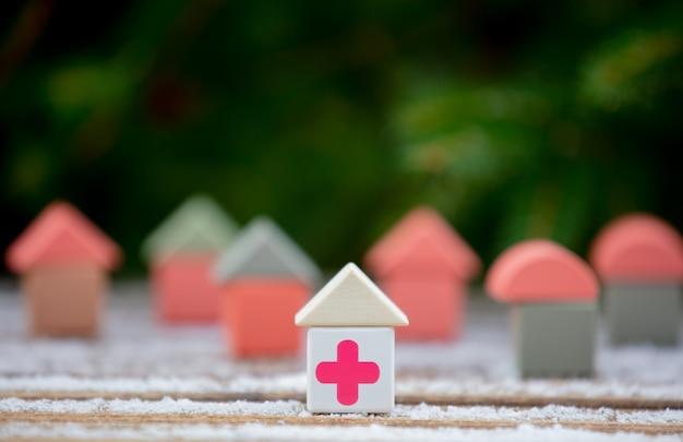 雪のテーブルに医療赤十字の小さなおもちゃの家