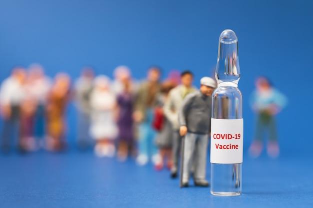 Маленькие игрушечные человечки и ампулы с вакциной люди стоят в очереди для вакцинации от коронавируса