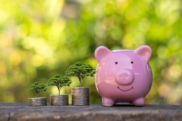 Little trees and pink piggy bank on wooden table with green leaves blurred background