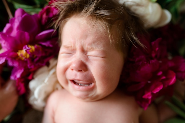 A little two-month-old girl lies on a wooden table with peonies and cries.