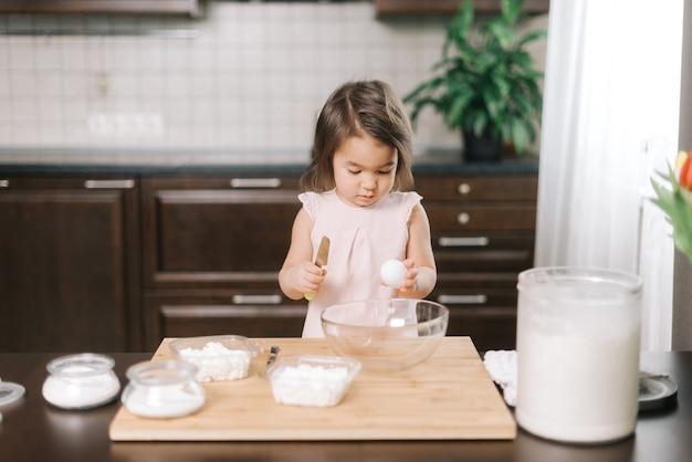 두 살짜리 어린 소녀가 계란을 깨고 서서 케이크를 굽는 법을 배우고 있다