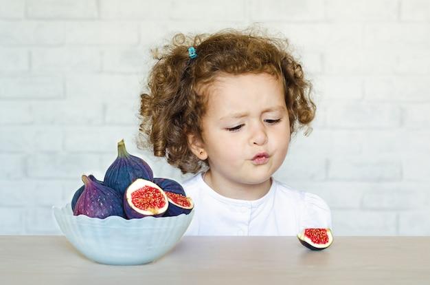 Маленький несчастный ребенок, девочка смотрит на инжир с неохотой и отвращением
