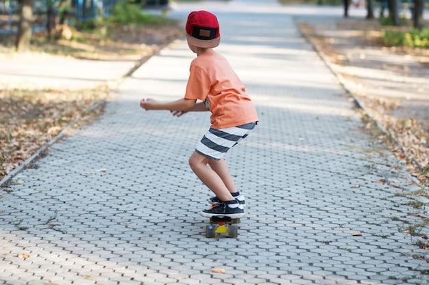 ペニースケートボードを持った小さな都会の少年。サマーパークでのキッズスケート