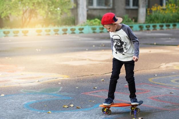ペニースケートボードを持った小さな都会の少年。スケートボードで公園に乗っている幼い子供