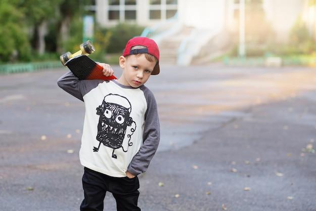 ペニースケートボードを持つ小さな都会の少年
