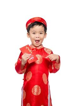 Маленький вьетнамский мальчик держит красные конверты для тет. слово означает двойное счастье. это подарок в лунный новый год или праздник тет на красном фоне изолировать.