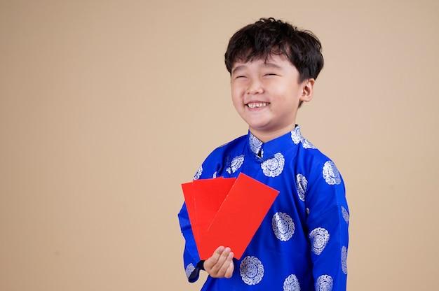 Little vietnamese boy holding red envelops for tet.