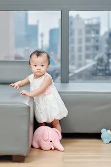 다양한 인형 장난감이있는 거실에서 노는 어린 베트남 소녀