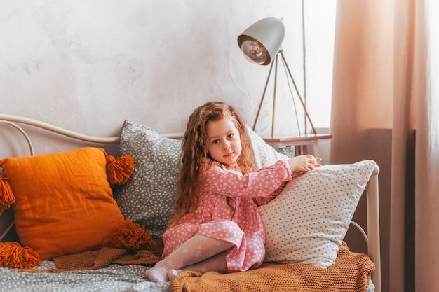 Маленькая винтажная девочка сидит на кровати в детской спальне и мечтает