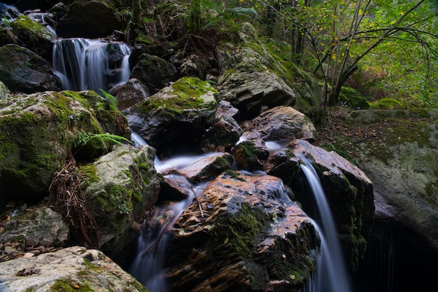 Little waterfall (named irusta) surronded by the forest of aiako harriak mountain at basque country.