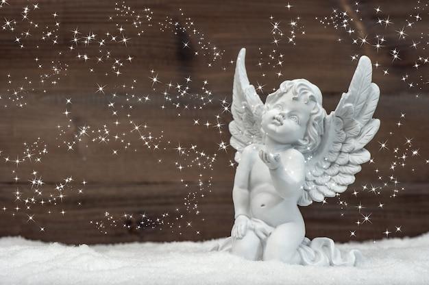 雪の中で魔法のライトを持つ小さな白い天使。クリスマスの飾り