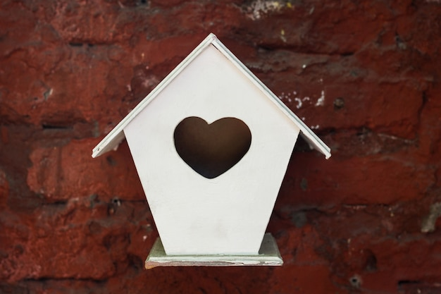 Little white birdhouse with heart symbol hole hanging from red brick wall. love birds home, valentine gift concepts