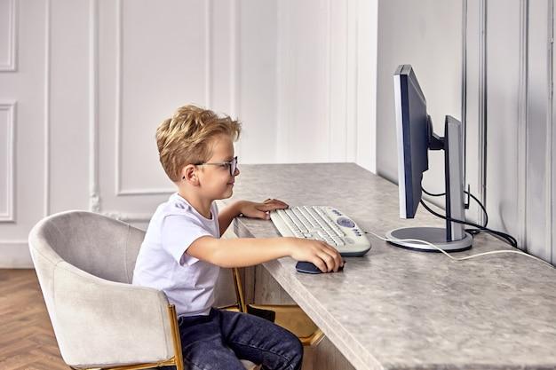 眼鏡をかけた6歳の小さな白人の男の子が、キーボードとコンピューターのマウスを近くに置いて笑顔でコンピューターの近くに座っています。
