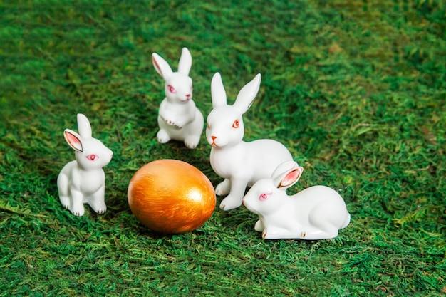 金の卵の周りの小さな白いウサギ