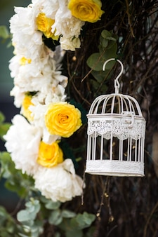 Little white cage hangs on the osier twined around wedding altar