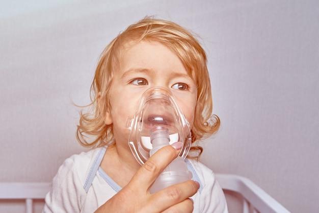Маленькая белая кавказская белокурая девочка около 2 лет с заболеванием легких дышит с медицинской маской, чтобы облегчить симптомы.