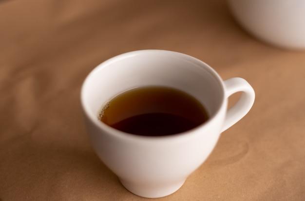 茶色の再生紙で覆われたテーブルの上のコーヒーと小さな白いコーヒーカップ