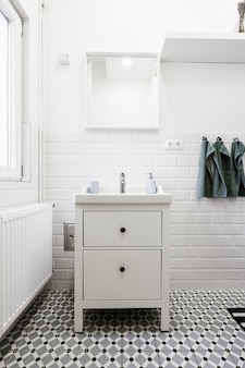 Little white drawer in a white bathroom with hygiene care items on it