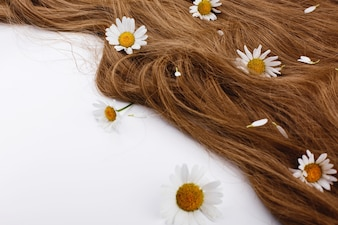 Little white flowers lie on the brown hair curls