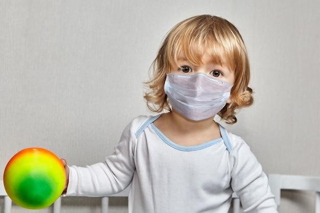 얼굴 마스크를 쓴 약 3 세의 어린 백인 소녀가 코로나 19 전염병 기간 동안 가정 격리에 공을 가지고 놀고 있습니다.