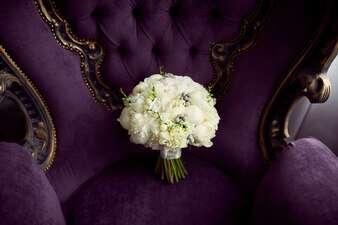 Little white wedding bouquet stands on violet chair