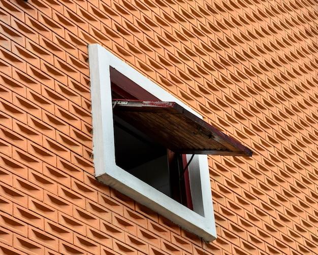 Little window at pattern orange brick cement wall