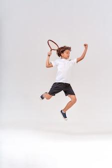 灰色の上に分離されたテニスラケットでジャンプする10代の少年の小さな勝者のフルレングスショット