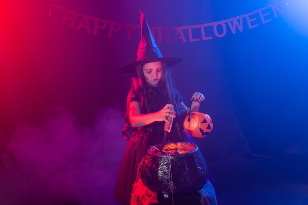 Little witch child cooking potion in the cauldron on halloween.