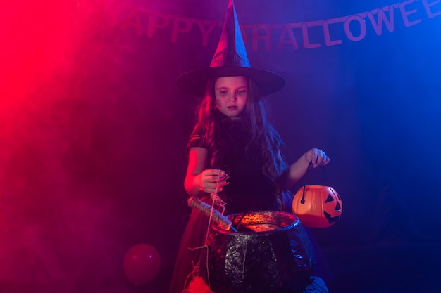 Little witch child cooking potion in the cauldron on halloween