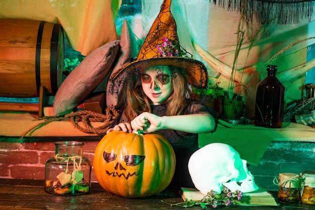 Маленькая ведьма, забавная ведьма с тыквой, милая маленькая девочка, одетая в костюмы на хэллоуин, веселится ...