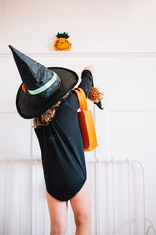 Little witch putting toys in bag