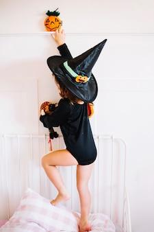 Little witch standing on pillow
