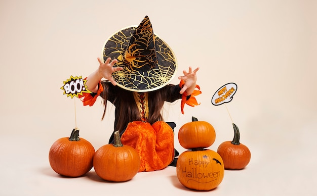 Little witch with halloween pumpkin